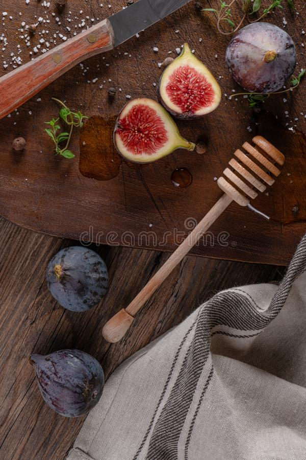 Fresh figs. Whole figs and sliced in half figs and thyme leaves on wooden cutting board royalty free stock images