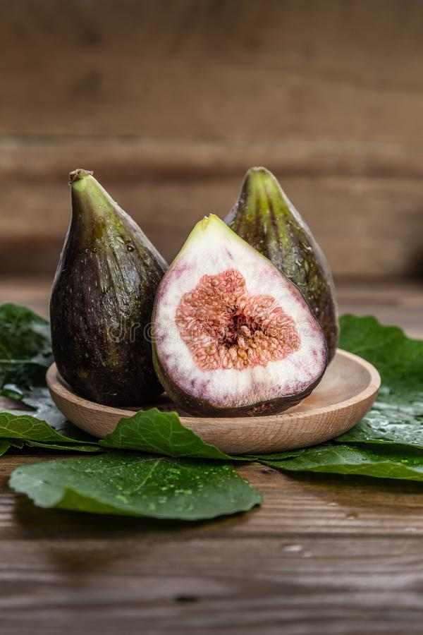 Fresh figs on wooden plate, with fig leaves, on wooden background. vertical format.  stock photo