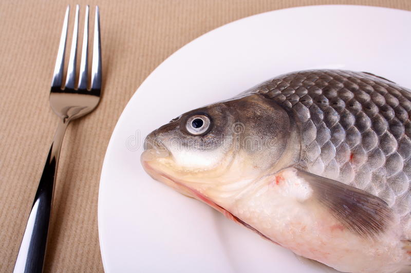 Fresh fish carp on white plate and fork royalty free stock image