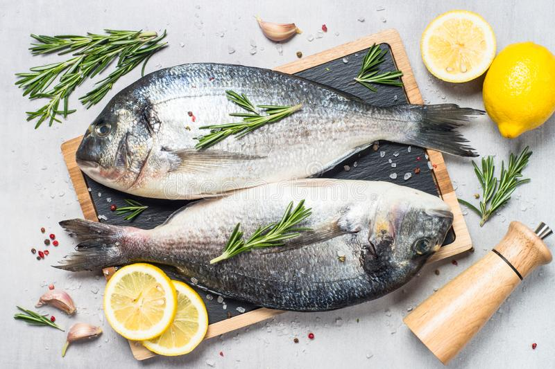 Fresh fish dorado on blue background. Fresh fish dorado on light stone background with lemon, rosemary and spices. Top view stock photo