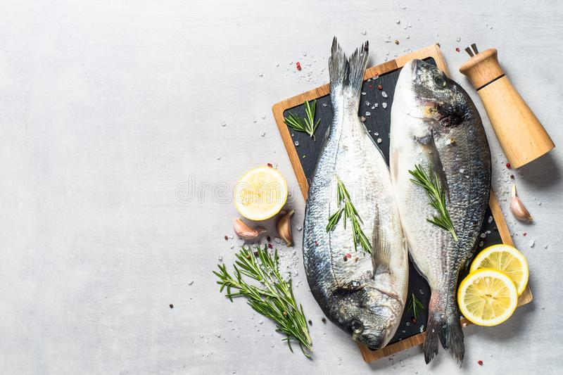 Fresh fish dorado on blue background. Fresh fish dorado on light stone background with lemon, rosemary and spices. Top view with space for text stock photos