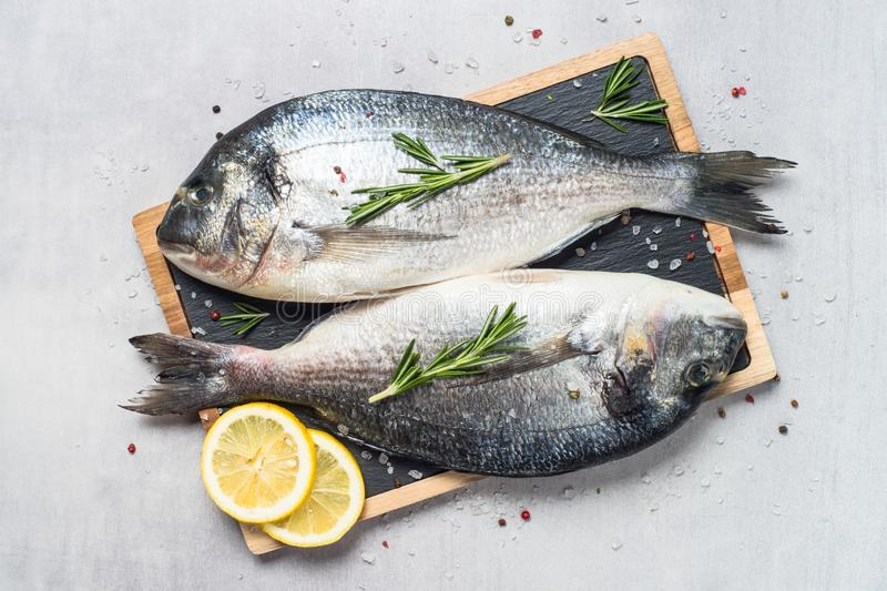 Fresh fish dorado on blue background. Fresh fish dorado on light stone background with lemon, rosemary and spices. Top view stock images