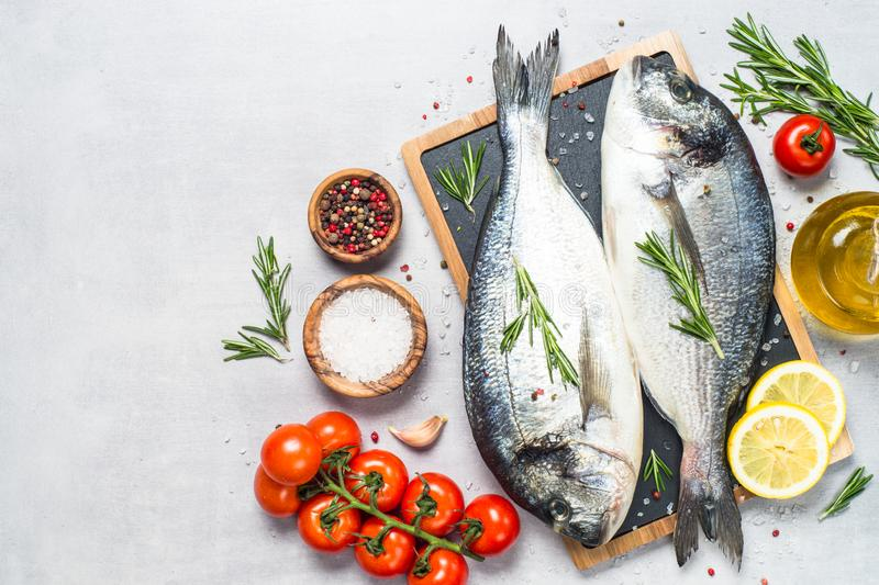 Fresh fish dorado on blue background. Fresh fish dorado on light stone background with lemon, rosemary and spices. Top view with space for text stock image