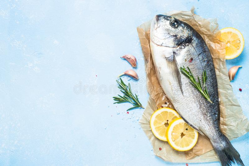 Fresh fish dorado on blue background. Fresh fish dorado on blue background with lemon, rosemary and spices. Top view with copy space royalty free stock photos