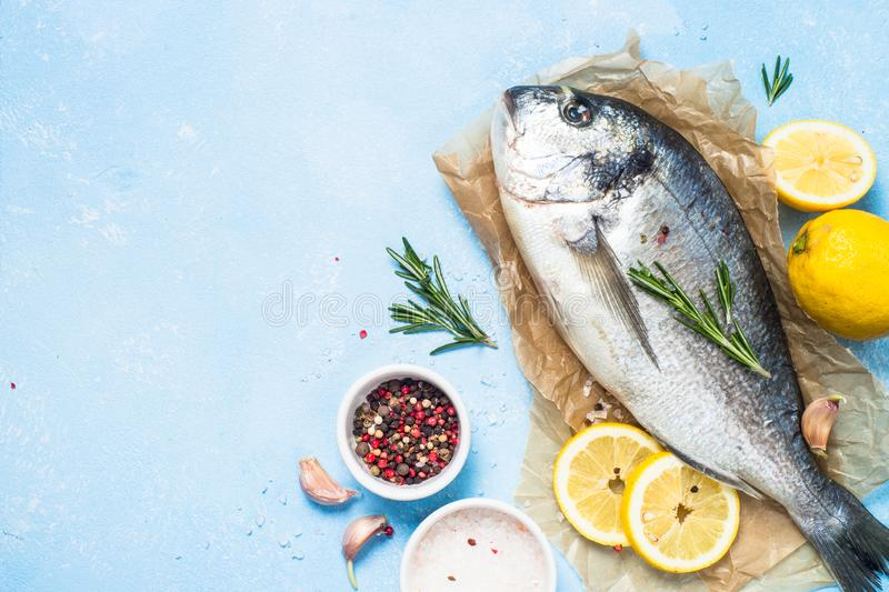 Fresh fish dorado on blue background. Fresh fish dorado on blue background with lemon, rosemary and spices. Top view with copy space royalty free stock photo