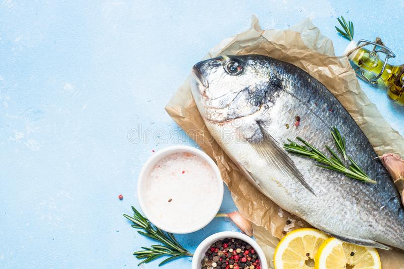 Fresh fish dorado on blue background. Fresh fish dorado on blue background with lemon, rosemary and spices. Top view with copy space royalty free stock image