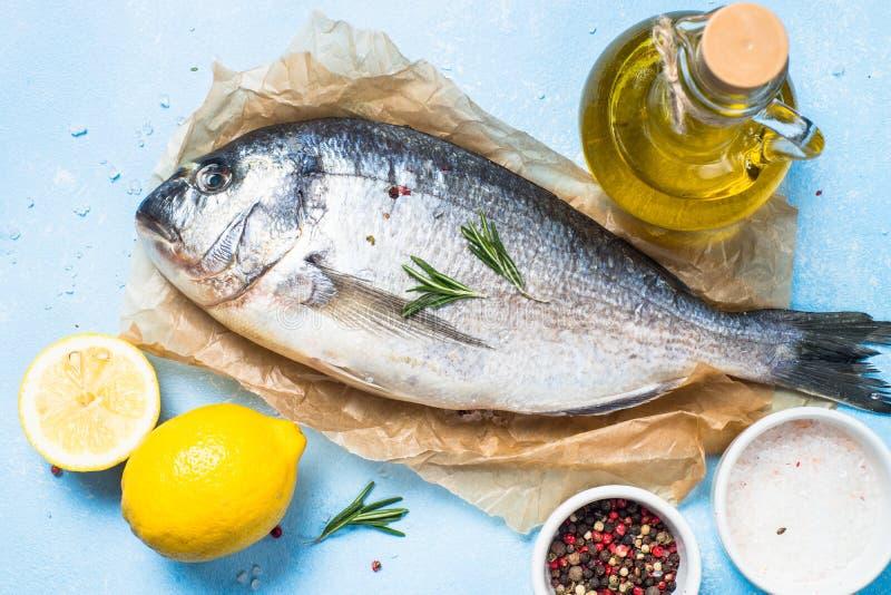 Fresh fish dorado on blue background. Fresh fish dorado on blue background with lemon, rosemary and spices. Top view stock image