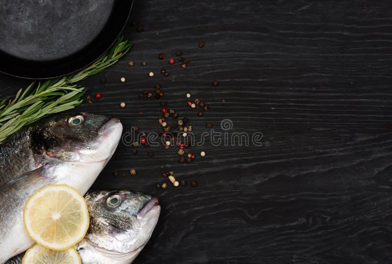 Fresh fish dorado. Dorado and ingredients for cooking on a table. Fresh fish dorado. Dorado and ingredients for cooking on a black table stock photos