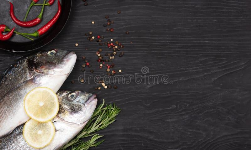 Fresh fish dorado. Dorado and ingredients for cooking on a table. Fresh fish dorado. Dorado and ingredients for cooking on a black table stock photography