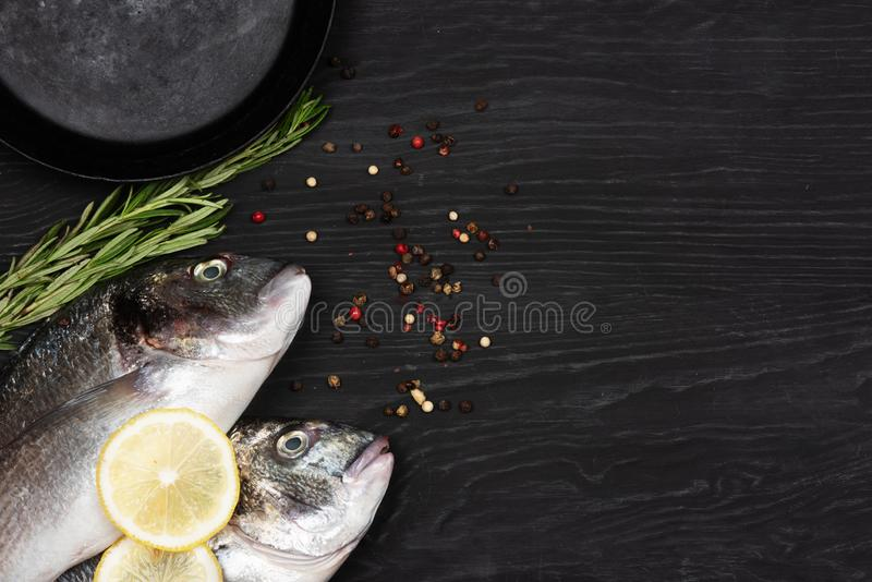 Fresh fish dorado. Dorado and ingredients for cooking on a table. Fresh fish dorado. Dorado and ingredients for cooking on a black table royalty free stock image