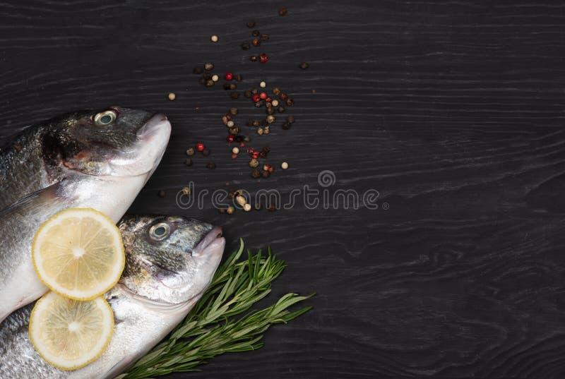 Fresh fish dorado. Dorado and ingredients for cooking on a table. Fresh fish dorado. Dorado and ingredients for cooking on a black table royalty free stock images