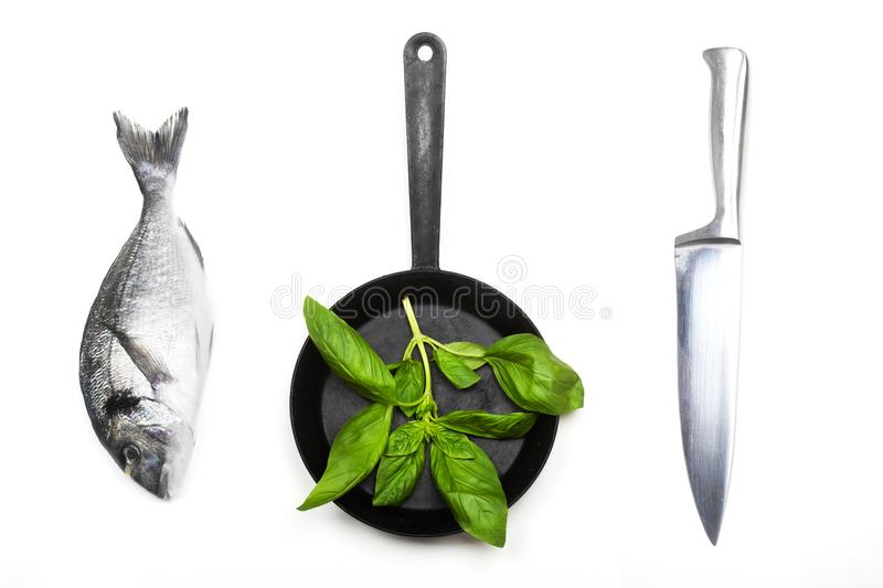 Fresh fish dorado, knife and frying pan. Fresh fish dorado, knife and frying pan with basil leaves on a white background. View from above royalty free stock image