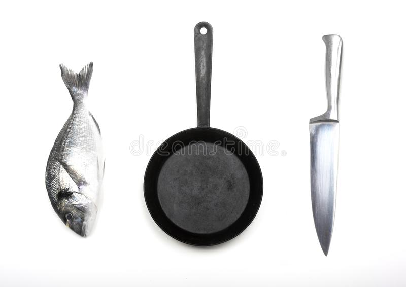 Fresh fish dorado, knife and frying pan. Fresh fish dorado, knife and frying pan on a white background. View from above royalty free stock images