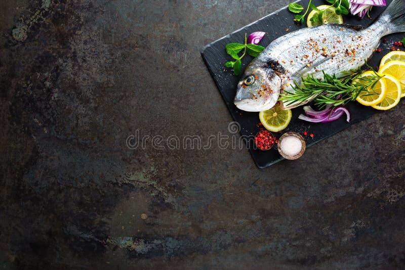 Fresh fish dorado. Raw dorado fish and ingredient for cooking on board. Sea bream or dorada fish on kitchen table stock photography
