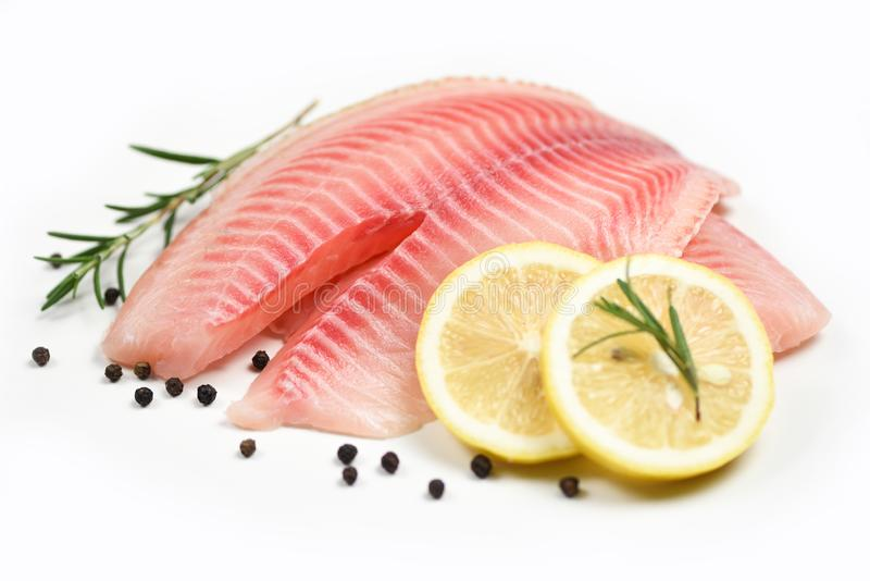 Fresh fish fillet sliced for steak or salad with herbs spices rosemary and lemon - Raw tilapia fillet fish on white background and stock image