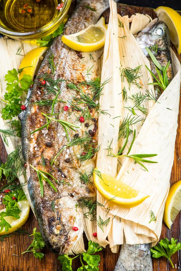 Fresh fish grilled in corn husk, healthy eating stock image