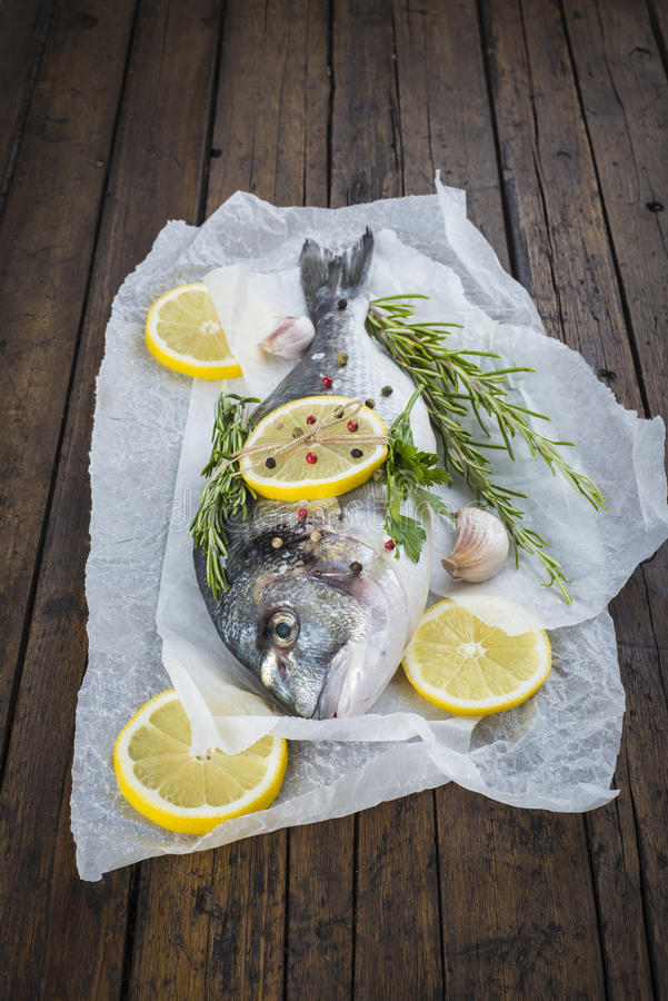 Fresh fish with lemon herbs and spices to cook. Fresh gilt-head sea bream fish with lemon herbs and spices on bakery release paper ready to be cooked stock images