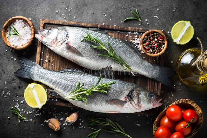 Fresh fish seabass on black. Fresh fish seabass and ingredients for cooking. Raw fish seabass with spices and herbs on black slate table. Top view stock photography