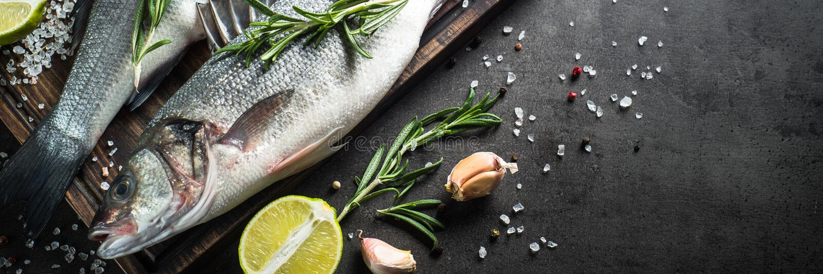 Fresh fish seabass on black. Fresh fish seabass and ingredients for cooking. Raw fish seabass with spices and herbs on black slate table. Long banner format royalty free stock image