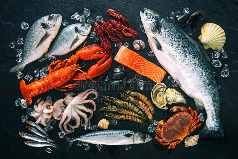 Fresh fish and seafood arrangement on black stone. Background royalty free stock photography