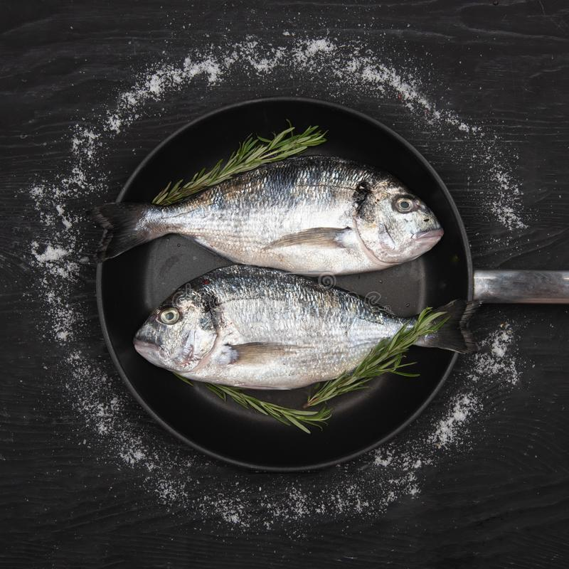 Fresh fixh dorado on a frying pan on a dark background. View from above stock photos