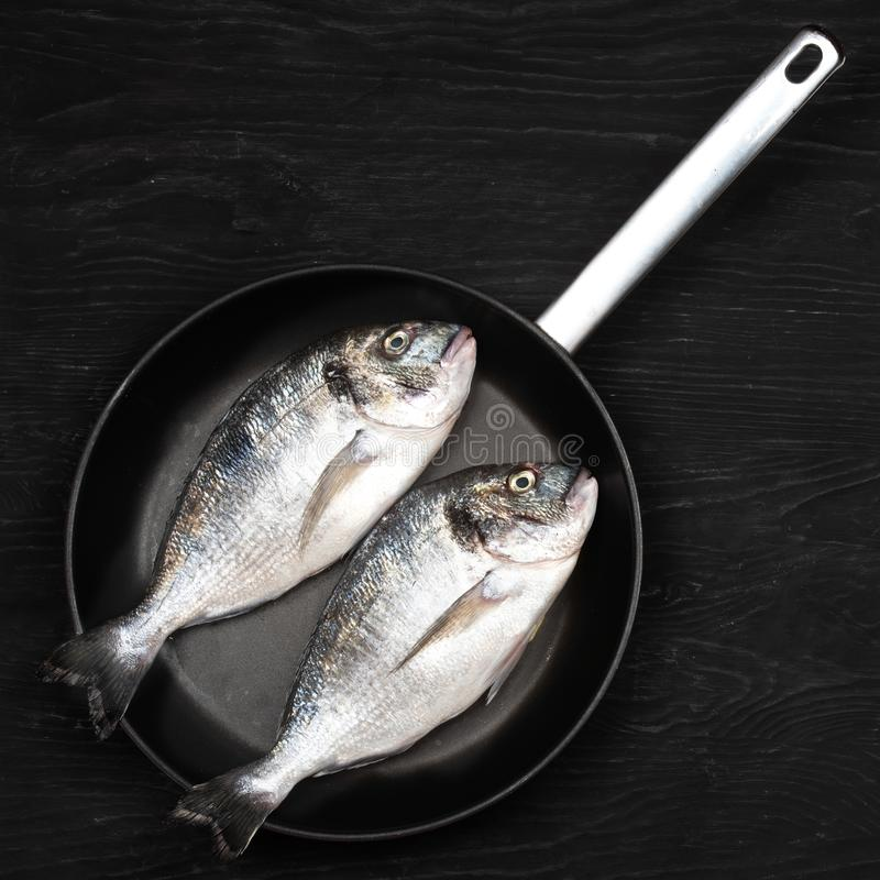 Fresh fixh dorado on a frying pan on a dark background. View from above royalty free stock photo