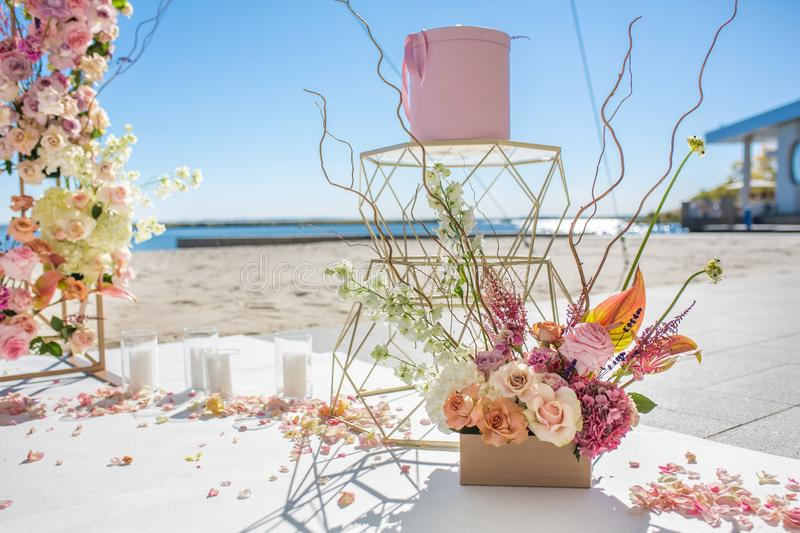 Fresh flower petals lie on the floor next to a decorated wedding arch and white candles. Event decoration with fresh flowers stock photo