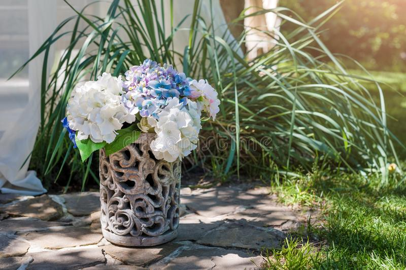 Fresh flowers arrangement in vase in the garden. Decorative bouquet for festive event. stock photography