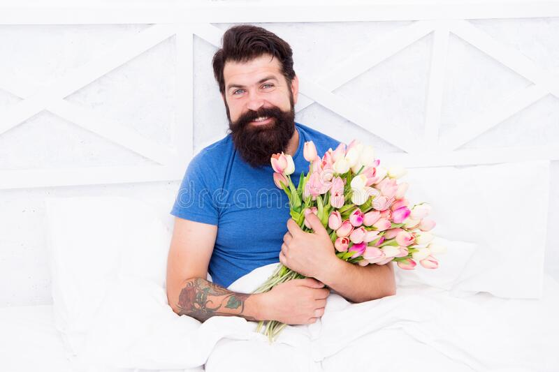 Fresh flowers surprise. Flowers delivery service. Birthday anniversary holiday. Gift for spouse. Bearded hipster in bed. Spring in bedroom. Man hold tulips royalty free stock photos
