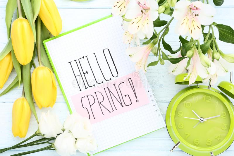 Flowers with text Hello Spring and alarm clock royalty free stock photo