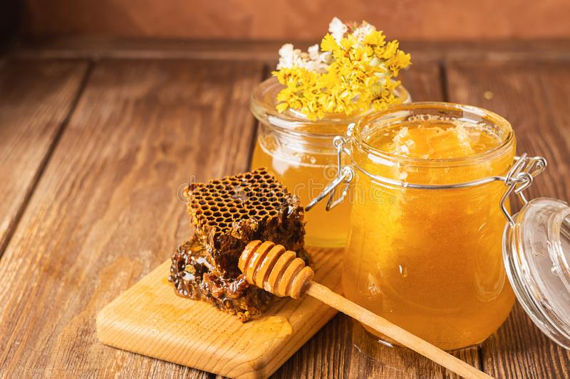 Fresh fragrant honey in a glass jar on a wooden background on the table. Different types of bee honey. Natural products. stock photography
