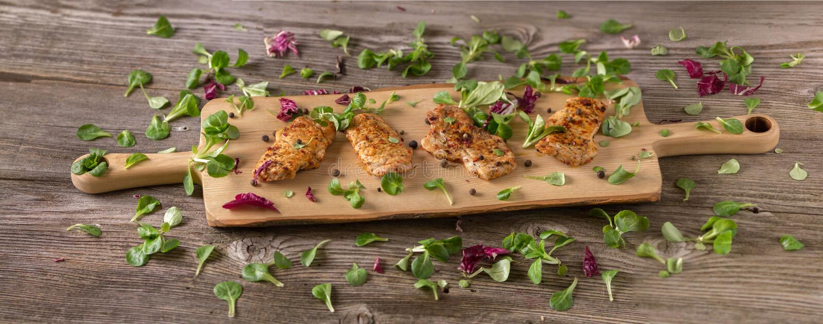 Fresh freshly fried delicious slices of meat on a wooden board with fresh herbs. Appetizing steaks on a wooden board. Banner for t. Fresh freshly fried delicious royalty free stock images