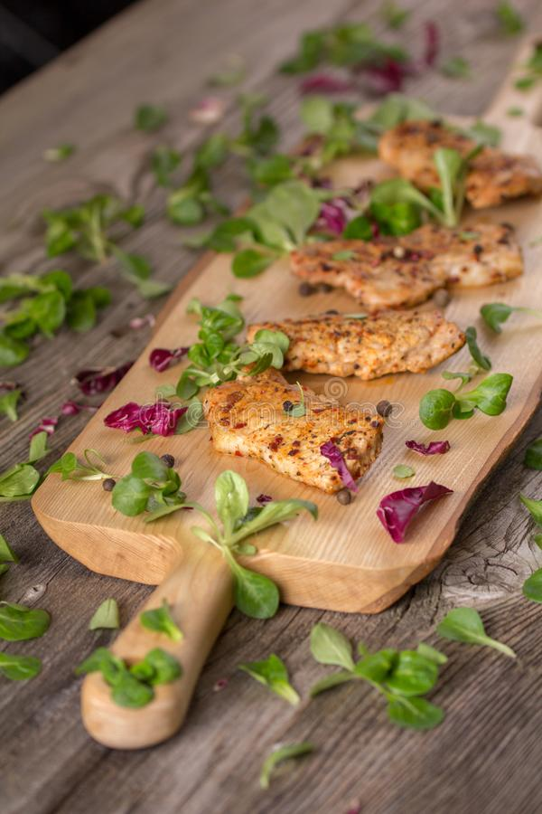Fresh freshly fried delicious slices of meat on a wooden board with fresh herbs. Appetizing steaks on a wooden board. Still life. Fresh freshly fried delicious stock images