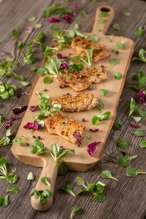 Fresh freshly fried delicious slices of meat on a wooden board with fresh herbs. Appetizing steaks on a wooden board. Still life. Fresh freshly fried delicious royalty free stock image