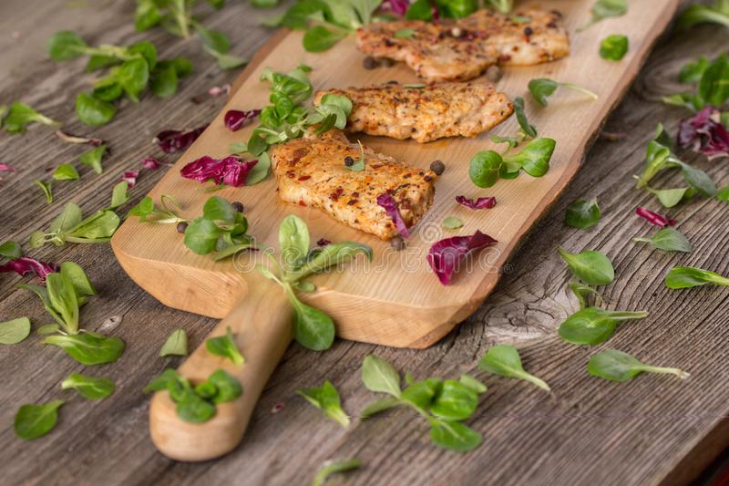 Fresh freshly fried delicious slices of meat on a wooden board with fresh herbs. Appetizing steaks on a wooden board. Still life. Fresh freshly fried delicious royalty free stock photo