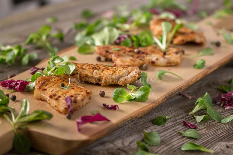 Fresh freshly fried delicious slices of meat on a wooden board with fresh herbs. Appetizing steaks on a wooden board. Still life. Fresh freshly fried delicious stock photos
