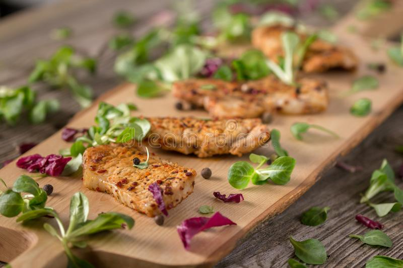 Fresh freshly fried delicious slices of meat on a wooden board with fresh herbs. Appetizing steaks on a wooden board. Still life. Fresh freshly fried delicious stock photo
