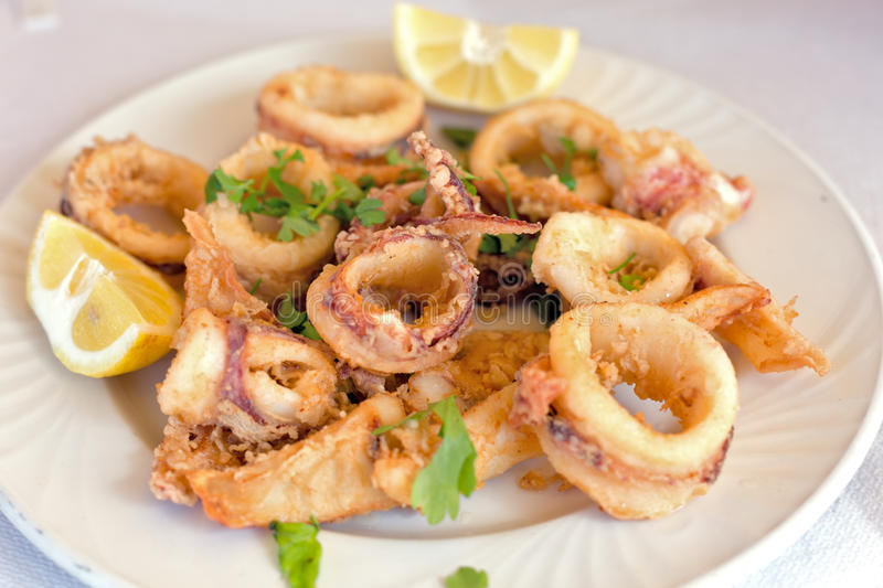 Fresh fried calamary rings. A plate of fresh fried calamary rings with lemon stock photography