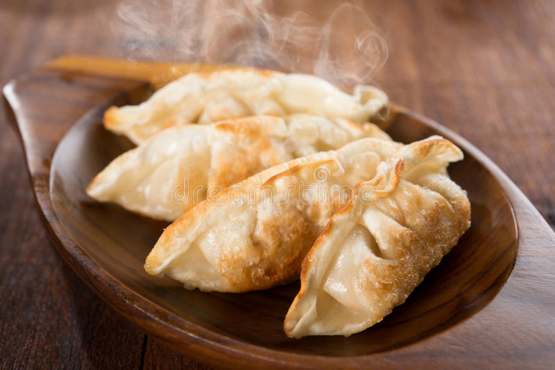Fresh fried dumplings. Fresh pan fried dumplings on plate with hot steams. Asian meal on rustic old vintage wooden background stock images