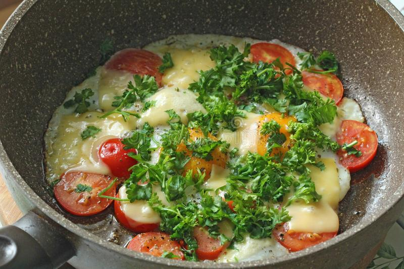 Fresh fried eggs are cooked in a frying pan, with tomatoes, cheese and greens. Vegetarian dishes. Bright healthy food.  royalty free stock images