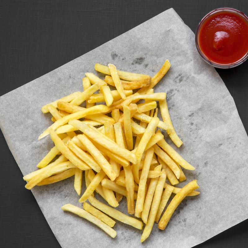 Fresh fried tasty french fries with sauce on a black background, overhead view. From above, top view.  royalty free stock photos