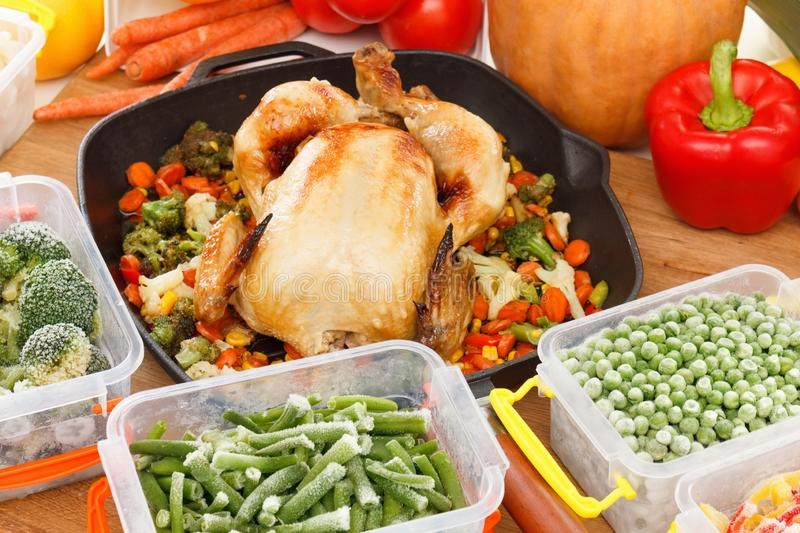 Fresh frozen vegetables and fried chicken food. Fresh frozen vegetables mixed in plastic containers, fried chicken in pan. Healthy freezer food and meals stock photo