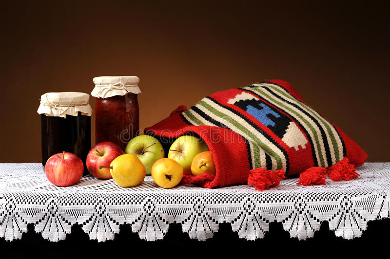 Fresh fruit in a bag of wool and jam in a jar royalty free stock photo
