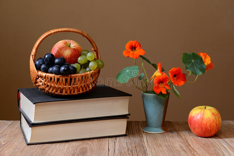 Fresh fruit in the of basket wicker, books and flowers royalty free stock images