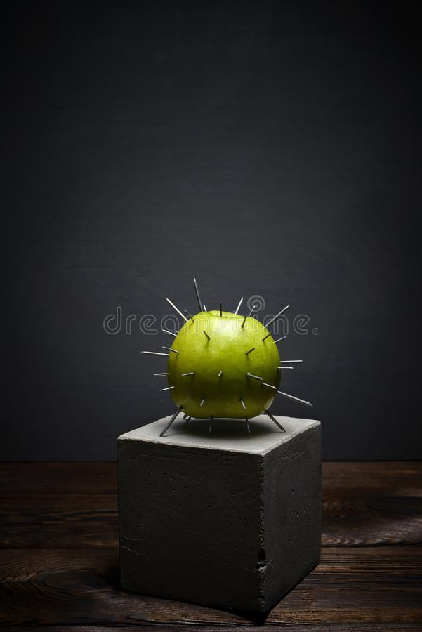 Fresh fruit on dark background on concrete stand. Green apple with sharp thorns royalty free stock photography