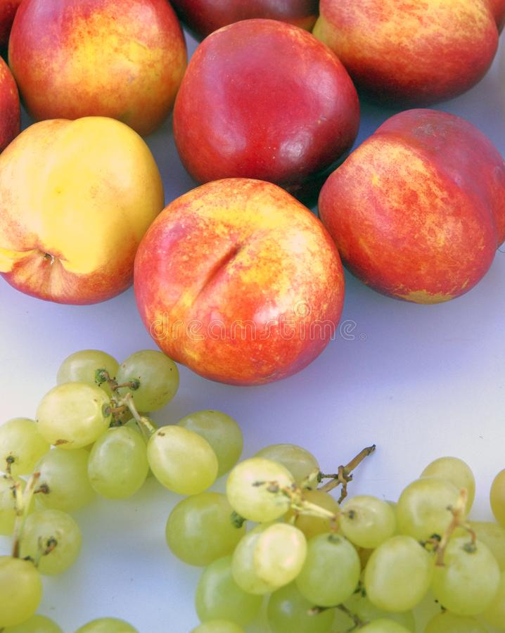 Fresh fruit excellent for your health, ready and cut: nectarine, grapes royalty free stock photos
