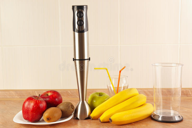 Fresh fruit, glasses and blender to prepare homemade smoothies royalty free stock images