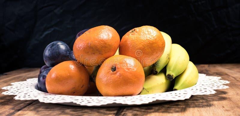 Fresh fruit orange, plum, banana, kiwi in the basket on a vintage wooden table stock photography
