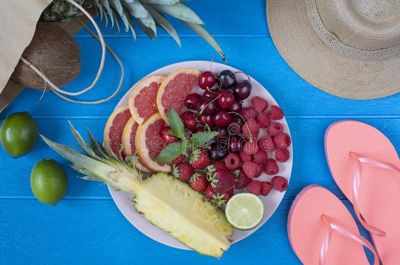 Fresh fruit plate and set of summer fashion beach accessories, top view from above overhead. Tropical beach lifestyle stock photos
