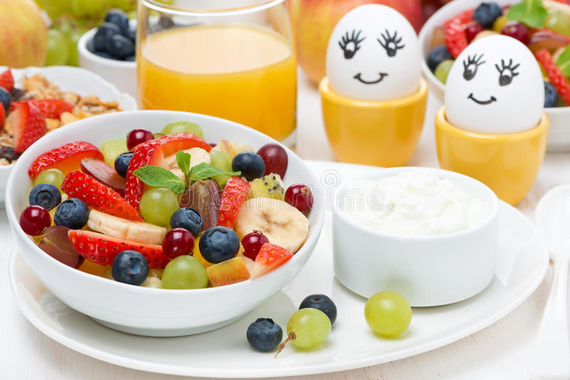 Fresh fruit salad, cream and painted eggs for breakfast stock image